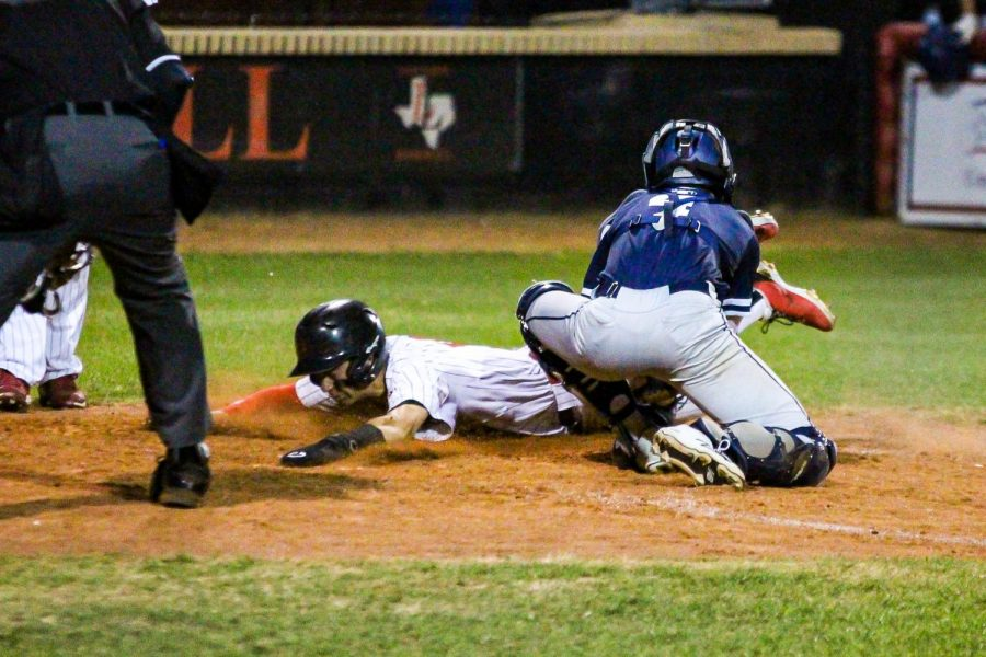 Junior shortstop no. 6 Kolby Branch dives into home safely, just beating out the tag. Kolby got on base after hitting a double down the left-field line.