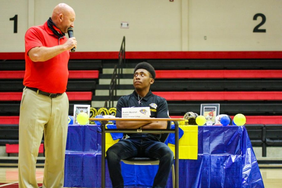 Senior baseball player Austin Marshall listens to head baseball coach Jason Wilson talk about him during the signing. Outfielder and second baseman Marshall will play baseball at Central Christian College.