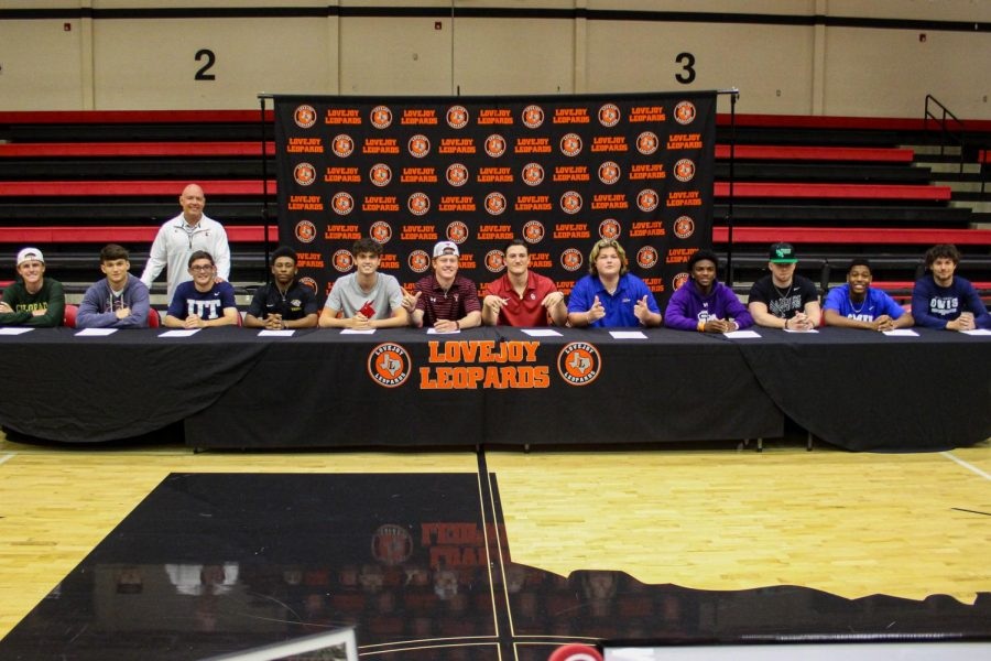 All twelve of the signees pose for a photo with Athletic director and head football coach Chris Ross after they sign their letters of intent. Boys from five different sports signed including baseball, football, basketball, golf and soccer.