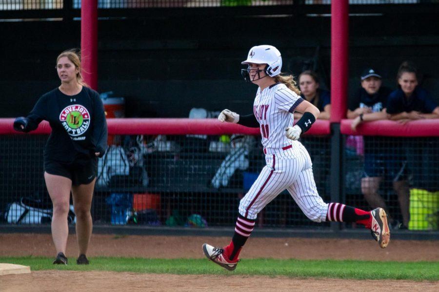 Sophomore second basemen no. 11 Hannah Harvey runs to first base after hitting.