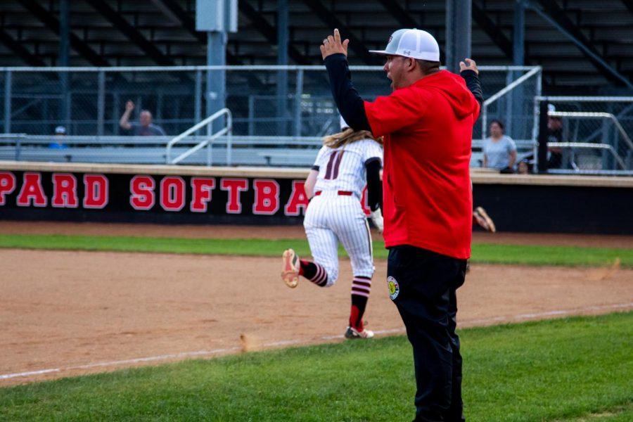 Head softball coach DJ Lopez cheers as sophomore second basemen no. 11 Hannah Harvey runs to home plate. The Leopards scored nine runs.