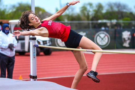 """Freshman high jumper and distance runner Caroline Dolberry glides over the high jump bar. Dolberry claimed first place for JV girl's high jump clearing 4'8""""."""