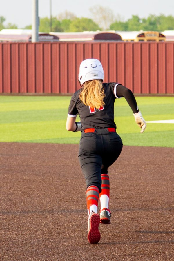 Sophomore second basemen no. 11 Hannah Harvey runs from first to second base. Harvey scored two runs in the game.