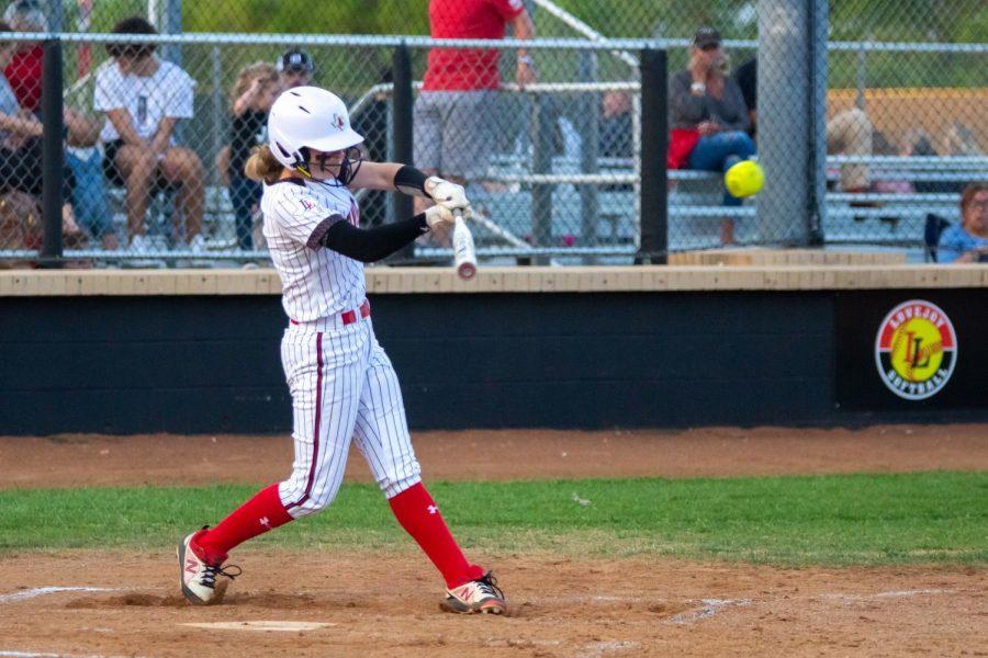 Sophomore second basemen no. 11 Hannah Harvey hits the ball. Harvey hit a home run during the third inning.