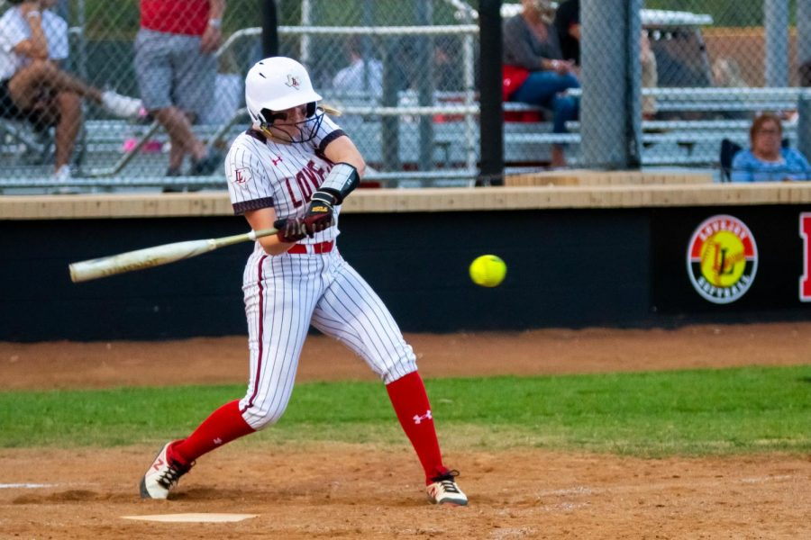Senior first basemen no. 4 Holly Massey swings for the ball. Massey got to third base on this run.