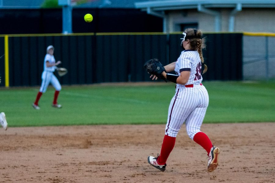 Junior third baseman no. 16 Emma Bittlestone throws to freshman short stop no. 5 Skylar Rucker. The Leopards won the game with a final score of 12-0.