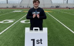 Senior Mason Stein holds his first-place medal after competing in the shot put event at the area track meet. Stein threw 51'2 at this meet to take the win.