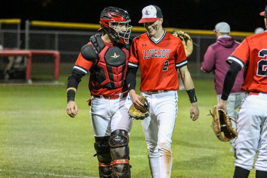 Junior pitcher no. 2 Trent Rucker receives a pat on the back from older brother; senior catcher no. 14 Ralph Rucker while heading into the dugout after the top of the third inning. Trent struck out two and threw out one in the inning for the three outs.