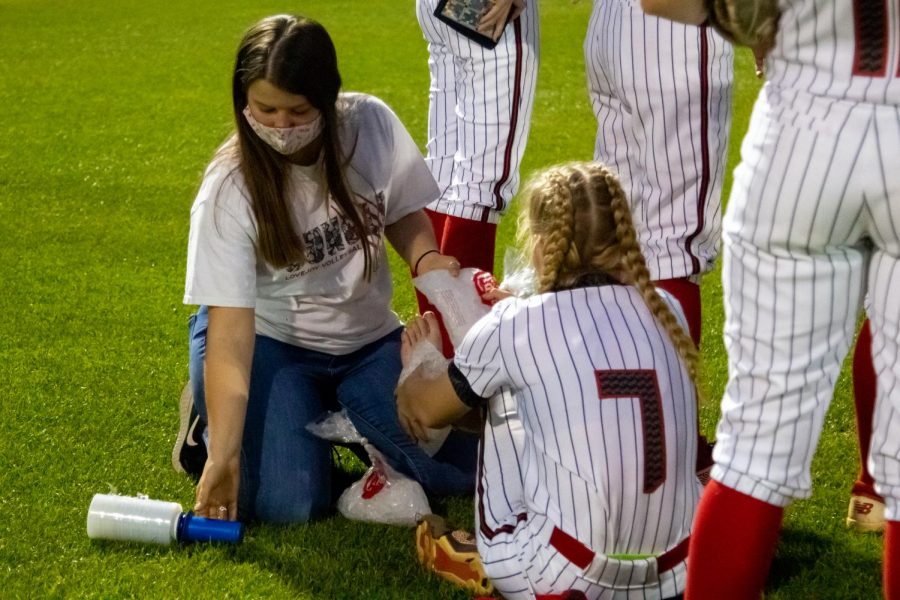 Senior athletic trainer Jenna Kilpatrick ices sophomore pitcher no. 7 Jade Owens foot after the game. Kilpatrick is the softball team's main athletic trainer.