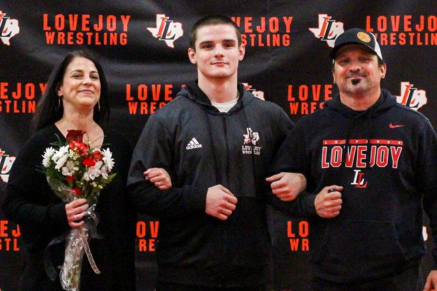Senior wrestler Jakob Underwood takes a picture with his parents on senior night. Underwood recently won his 100th wrestling match.