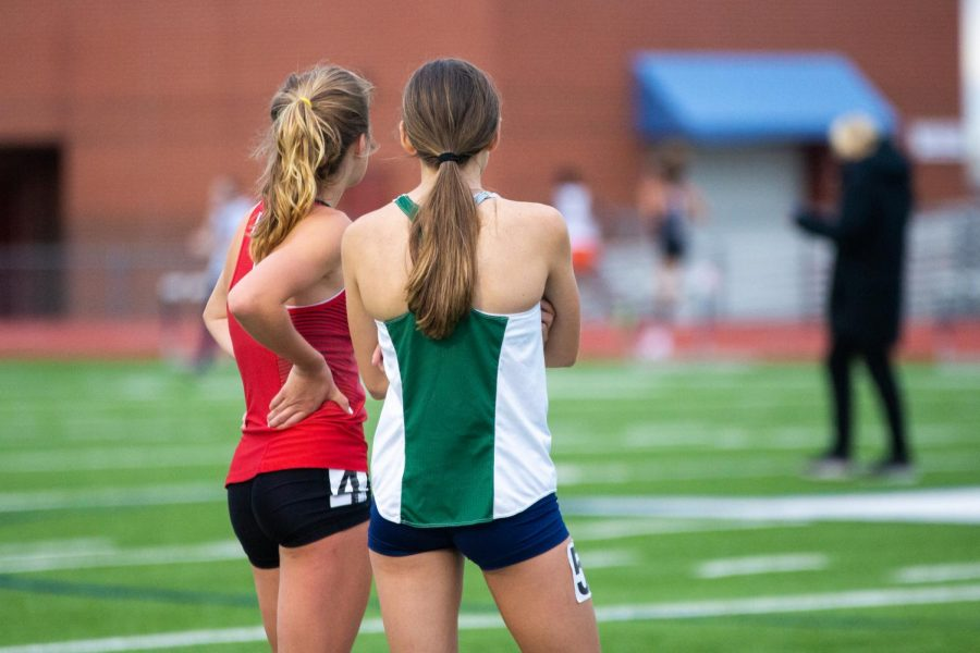 Sophomore runner Amy Morefield and Reedy's Coleen Stegmann watch the boys 3200 meter race. Stegmann won the girls 3200 meter race and Morefield placed in fourth.