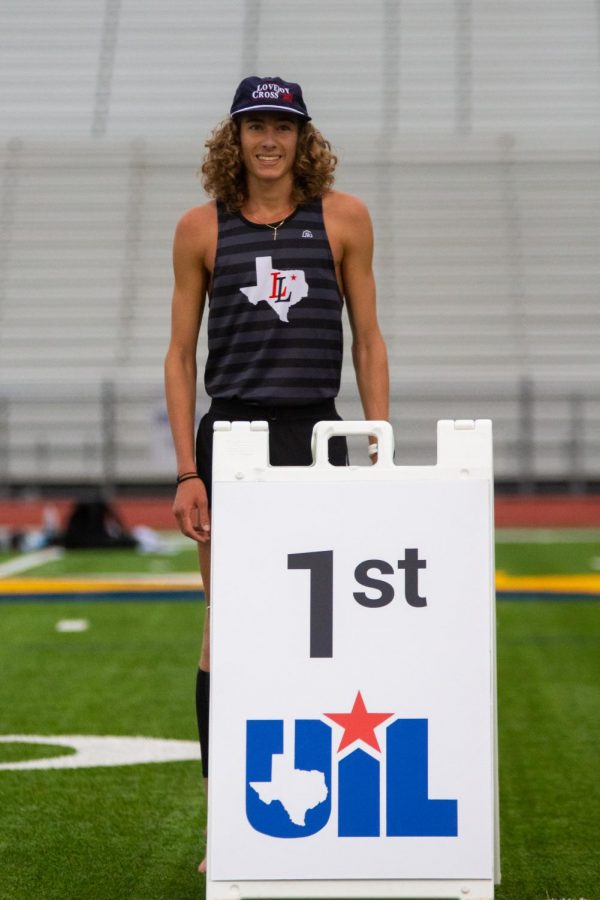 Junior runner Tate Barr stand behind the first place sign after winning the 3200 meter race. Barr qualified for the 3200 meter and 1600 meter races at region.