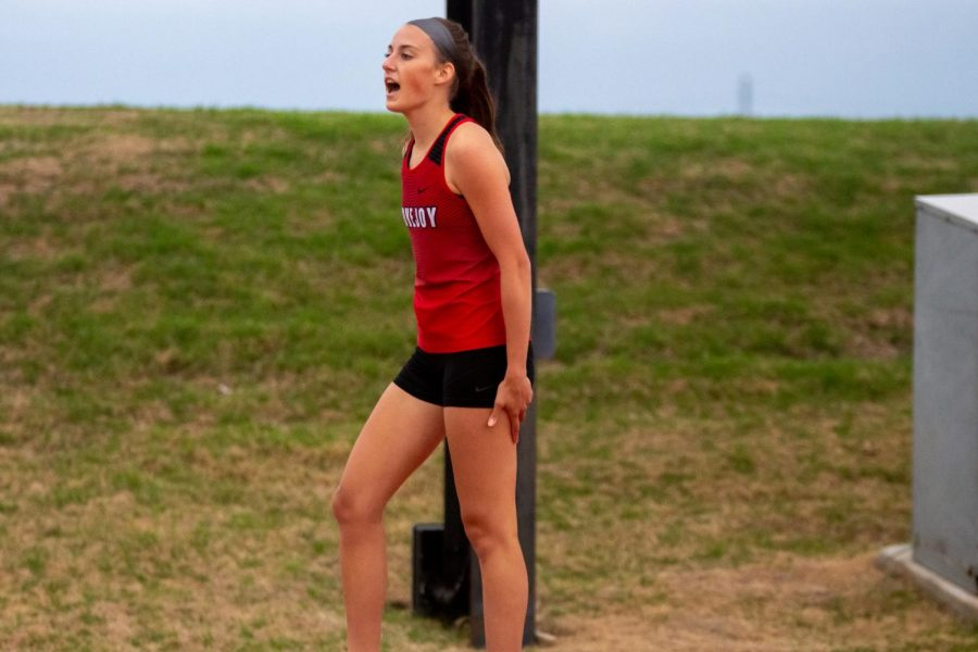 Freshmen runner Lauren Dolberry cheers for relay teammate freshmen Madeline Smith. The girls 4x200 team placed in sixth behind Frisco Lone Star.