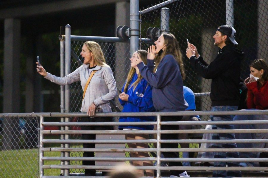 Junior runner Tate Barr's parents and sister, Anna, cheer Tate on while recording his 1600 meter run. Barr placed second in this race followed by junior Matt Murray.
