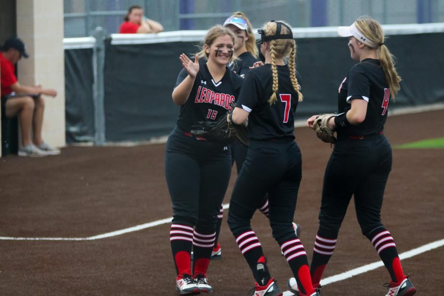 Junior third baseman no. 16 Emma Bittlestone celebrates an inning with no runs scored with sophomore pitcher no. 7 Jade Owens. The Leopards are playing the Wolverines in a three-game series for the first round of playoffs.