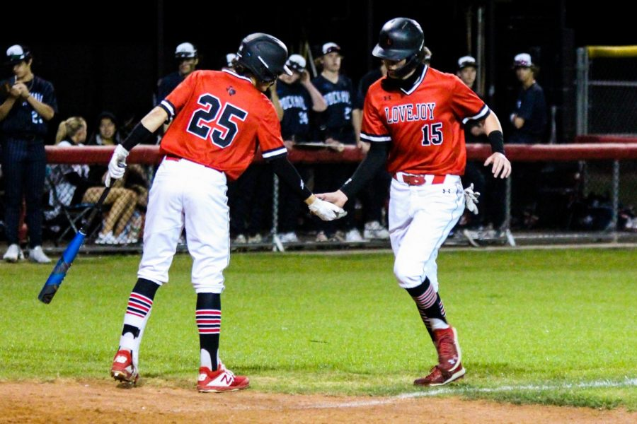 Senior third baseman no. 15 Dylan Collins high fives freshman second baseman no. 25 Kyle Branch as he crosses the plate. A balk was called during Branch's at bat against Rockhill's junior pitcher no. 12 Drew Rogers which caused Collin's run.