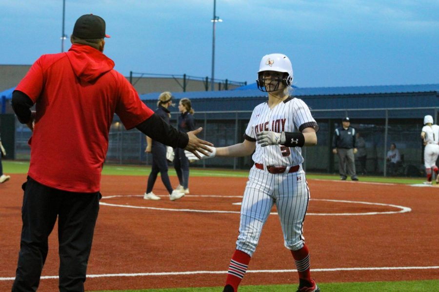 Sophomore catcher no. 3 Sydney Bardwell high fives head coach DJ Lopez after making a run to home base. The Leopards had scored two runs in the fourth inning.