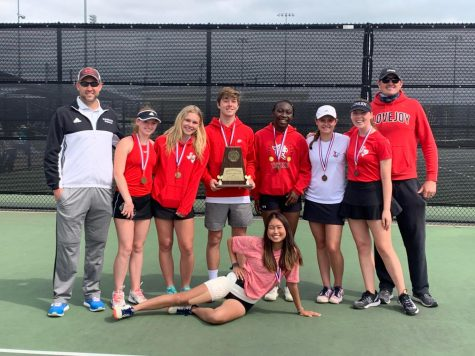The tennis team poses with their district trophy. The tennis team will be competing in the regional tournament on April 27 and 28.
