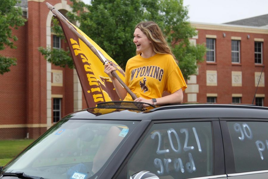 Senior Lexie Collins rides in the parade holding a Wyoming flag. Collins committed to play volleyball for the University of Wyoming.