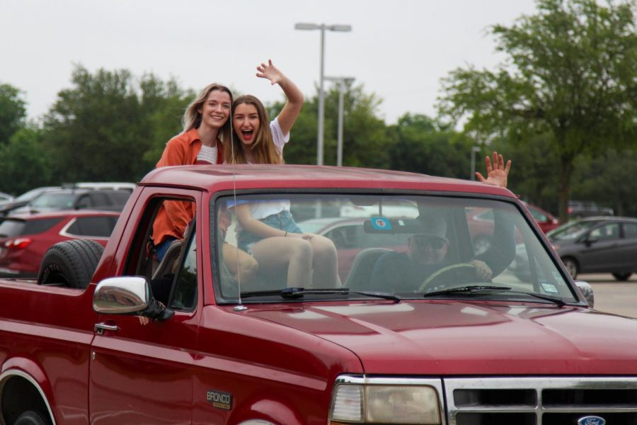 Peyton and Paige White ride in the back of a truck for the parade. Graduation will take place this Saturday.