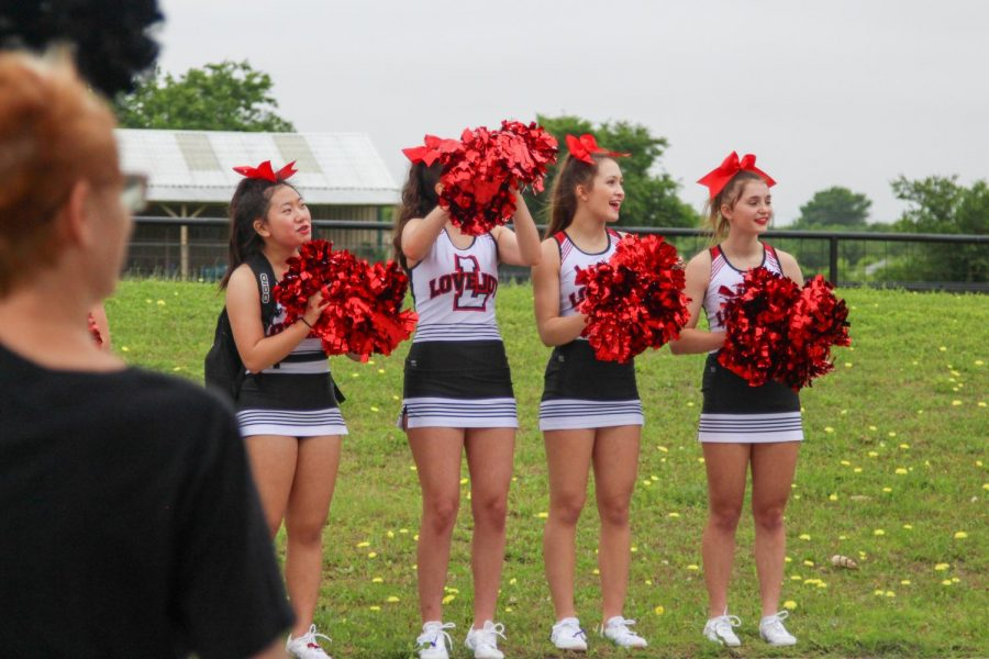 Sophomore cheerleaders Evelyn Kwon, Sydney Decarlo, Isabel Szymanski, and Makenzie Lang cheer for the seniors as they drive by. The four are part of the varsity team next year.