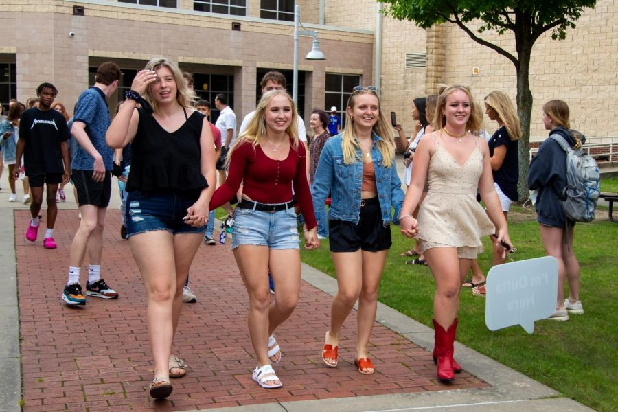 Seniors Sarah Jean Clements, Taylor Crosby, Mackenzie Hall, and JJ Tribuna hold hands during senior walk. Clements will be attending the Univeristy of Colorado at Colorado Springs.