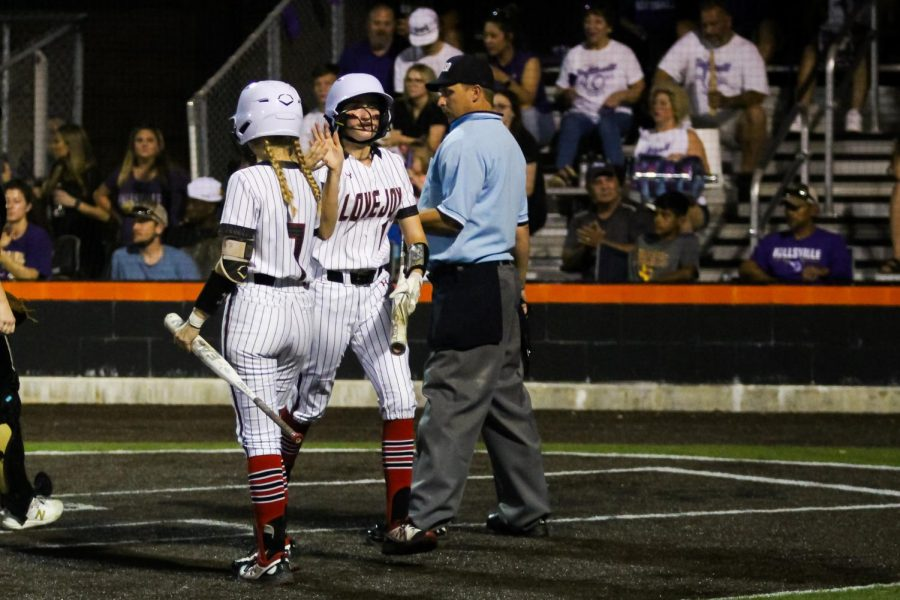 Sophomore pitcher no. 7 Jade Owens high fives junior right fielder no. 18 Bailey Bradshaw. Bradshaw scored the fourth run for the Leopards.