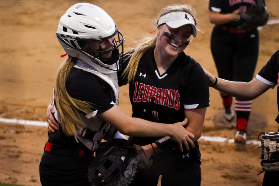 Sophomore catcher no. 3 Sydney Bardwell and senior first basemen no. 4 Holly Massey hug each other after the sixth inning. The Leopards won the first game with a final score of 4-2.