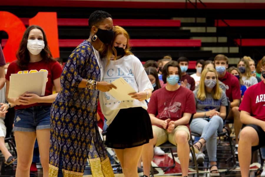 Camille Simpkins gives senior Taryn Sutherlin a scholarship she received. Sutherlin will be attending the University of California, Los Angeles.