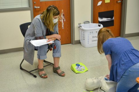 Health Science teacher Kathryn Barnett watches junior Maci Perkins practice for her CPR certification test. Barnett teaches Principles of Health Science, Pharmacy Tech, and part of the CNA Collin College course.
