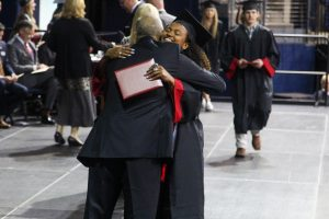 Graduate Cecily Bramschreiber hugs Principal Chris Mayfield. Bramschreiber graduated in December and has been playing volleyball for Texas Christian University.