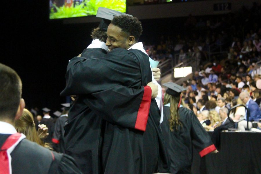 Graduate Reid Westervelt hugs Coach Brandon Jackson before walking to the stage. Westervelt will be playing football for Rice University in the fall.