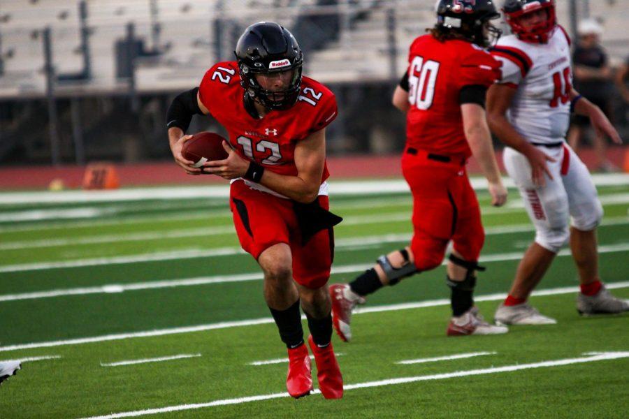 Junior quarterback no. 12 Brandon Hagle runs the football. The final game score was 54-0.