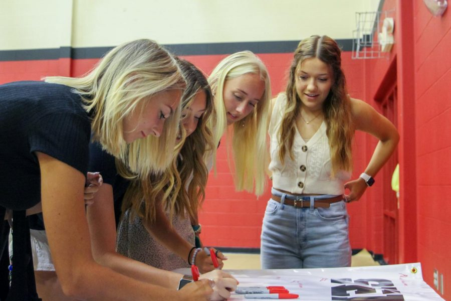 Seniors Mia Anderson, Katelyn Lanman, Taylor Kate Pickett, and Gina Peoples sign the senior banner. Peoples is the first lieutenant of the Majestics.