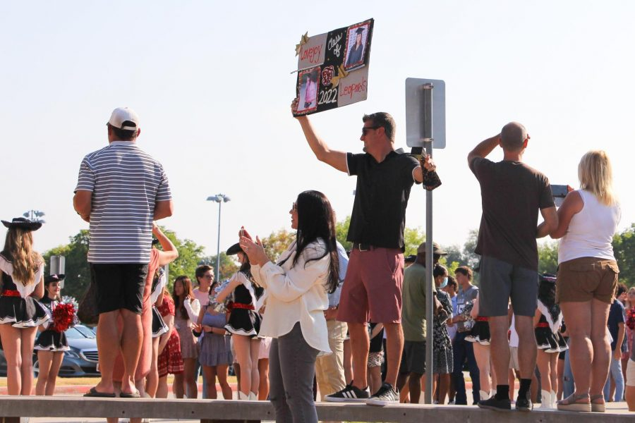 Senior Gwyn Freels' dad holds up a sign to cheer his daughter on. This event is annual for the seniors.