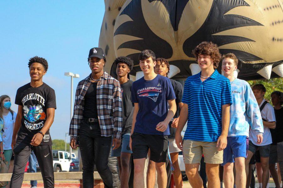 Seniors Taiden Connor, Joe Wilson, Kidus Getenet, Marco Gaccione, Trey Pugh, Jax Thompson, and Garrett Norwood walk as a group. All of them play basketball for the school.