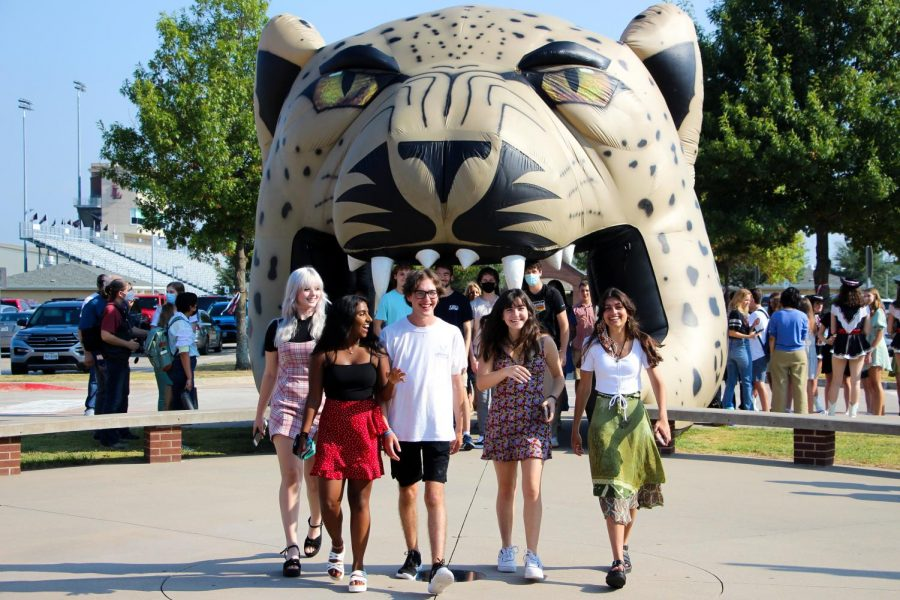 Seniors Avery Hayward, Dinah Thatikonda, Jake Pickens, Carly Roth, and Savannah Fanous walk past the leopard head. Roth is in Mock Trial.