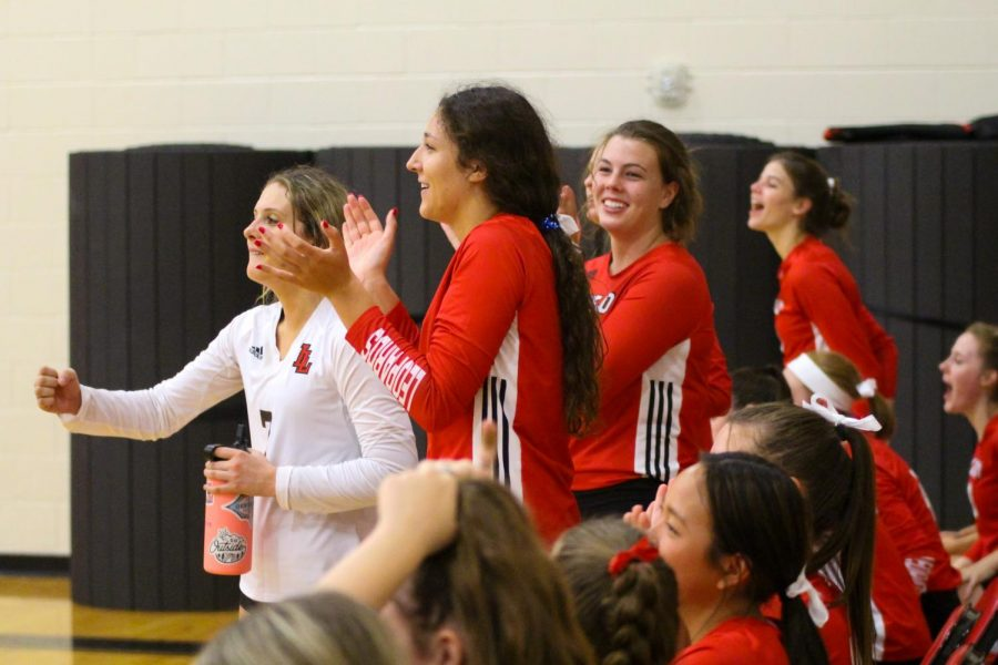 The Leopard's bench celebrates after scoring a point in the first set. Junior hitter no. 12 Hannah Gonzalez, senior libero no. 7 Ava Camacho, and sophomore outside hitter no. 20 Reagan Fitzsimmons stand to cheer on their team.