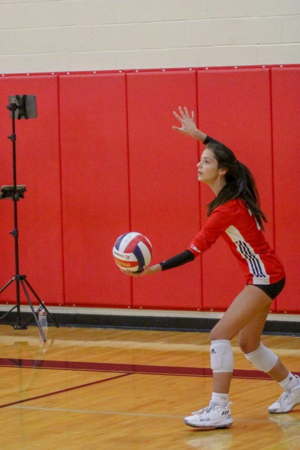 Sophomore defensive specialist no. 21 Isa Camacho prepares to serve the ball late in the game. This rally brought the score to 12-4 Leopards in the third set.
