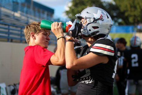 Sophomore athletic trainer Carson Brantl gives water to sophomore wide receiver no. 88 Colgin Pettit. Brantl was also a football trainer last year.