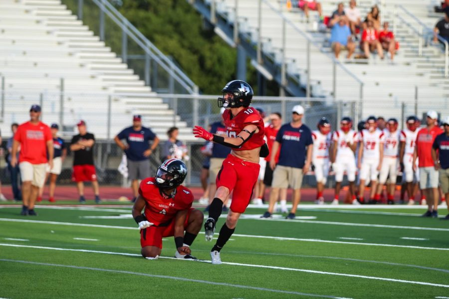 Senior running back no. 4 Noah Naidoo holds the ball as senior kicker no. 10 Trent Rucker kicks a field goal. Ruckers kick was complete for an extra point.