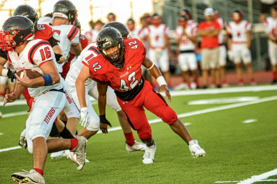 Senior outside linebacker no. 42 Daely Phillips goes in to tackle Centinnial's no. 16. The Leopards scored 8 touchdowns.