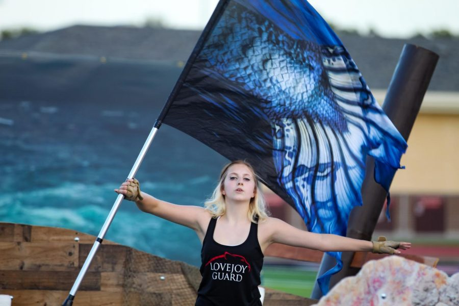 """Junior guard member Hannah Stout turns the flag. Stout has been a color guard member for five years performing in both programs """"Juliet"""" and """"Siren."""""""