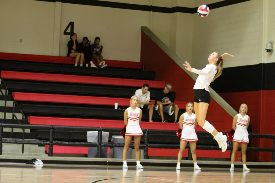Senior setter no. 9 Averi Carlson serves the ball. Carlson's serve was an ace giving the Leopards a lead on Hebron.