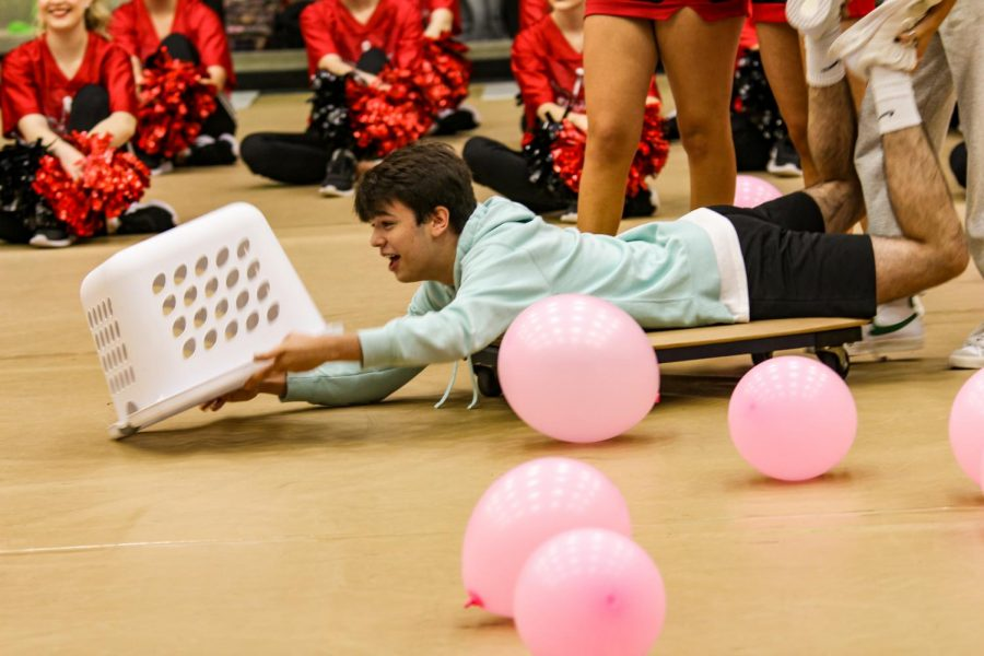 Sophomore Ryan Rolfe tries catching balloons to win the game. Rolfe was partnered with sophomore Zoe Smithey.