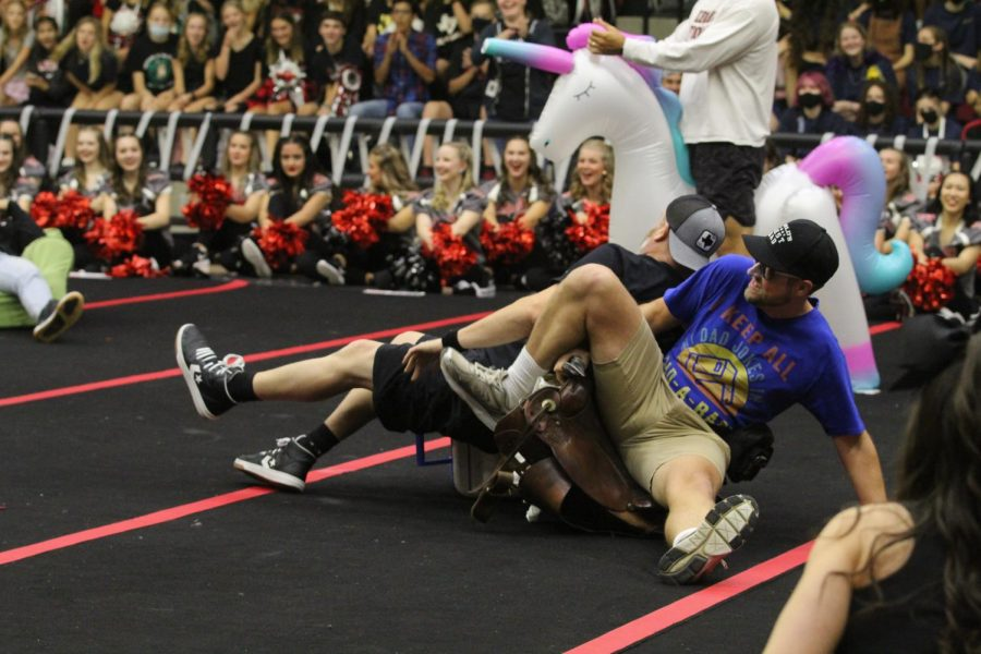Yearbook teacher Aaron Capatelli and history teacher Tim Daugherty attempt to take the saddle chair. Daugherty got the saddle.