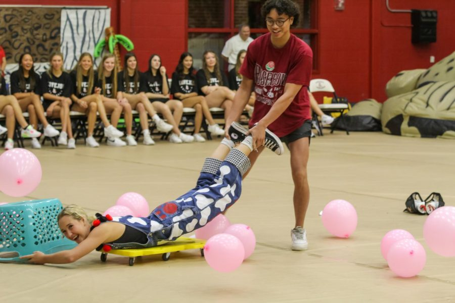 """Senior Derek Dang pushes senior Tatum Chester on a scooter for the game. The pep rally game was """"Hungry Hippos"""" with balloons and baskets."""