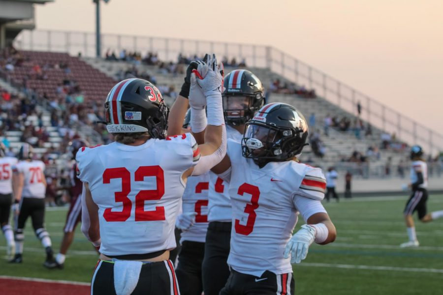 Sophomore running back no. 32 Matthew Mainord, senior running back Noah Naidoo, and junior offensive linemen no. 75 Noah Gardner celebrate after Mainord scored a touchdown. The first quarter concluded with a score of 14-0.