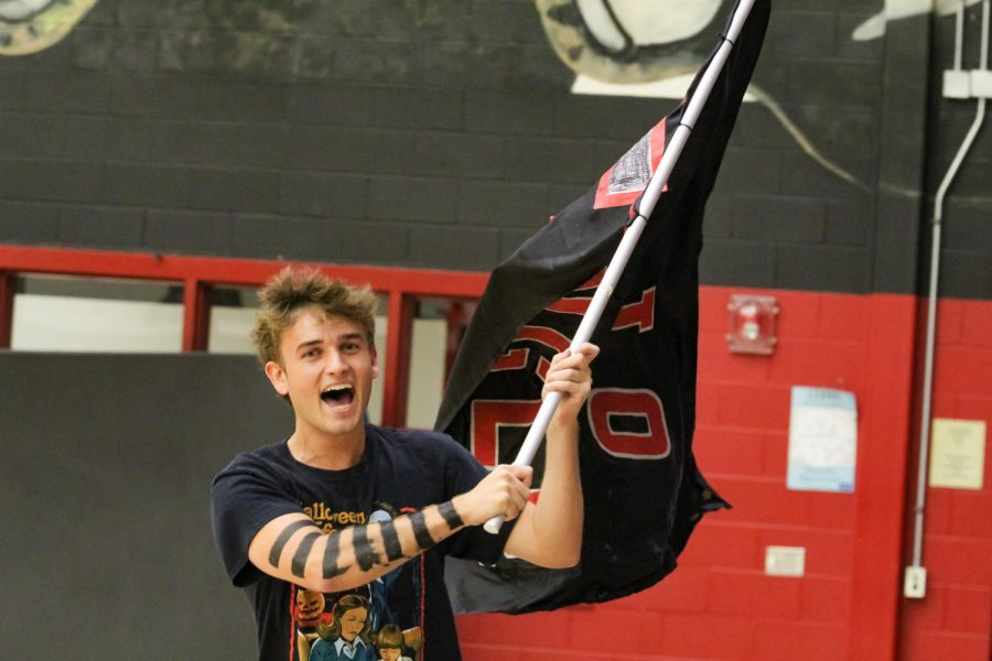 Senior Luke Fisher runs the flag in front of the crowd. The seniors hyped up the team with signs, flags, and megaphones.