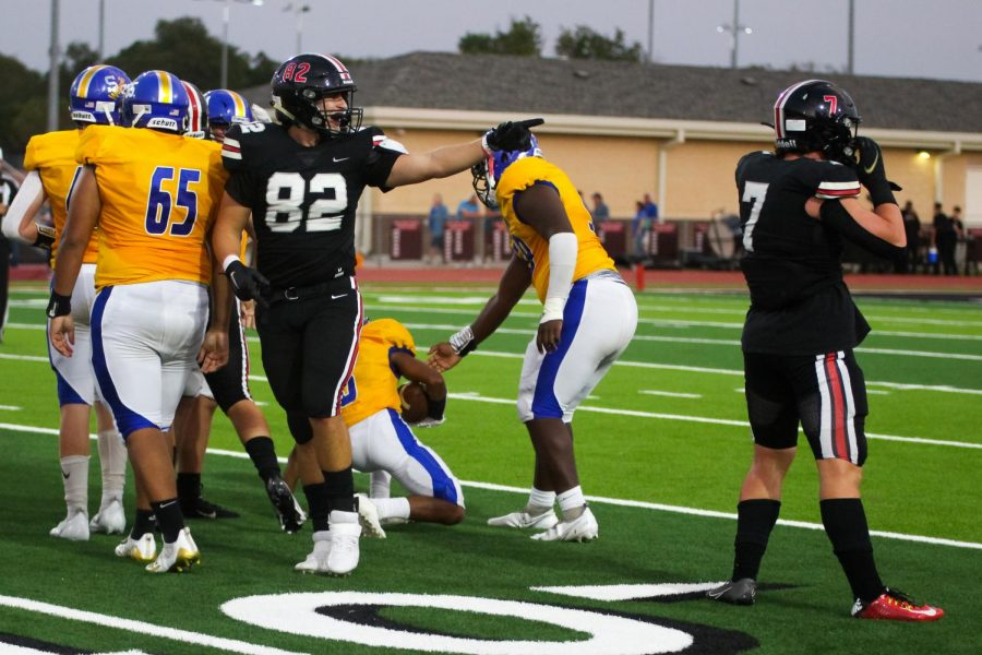 Sophomore defensive linemen no. 82 Nick Perez points out to the sidelines. Perez got a tackle for a Wildcat loss of yards.